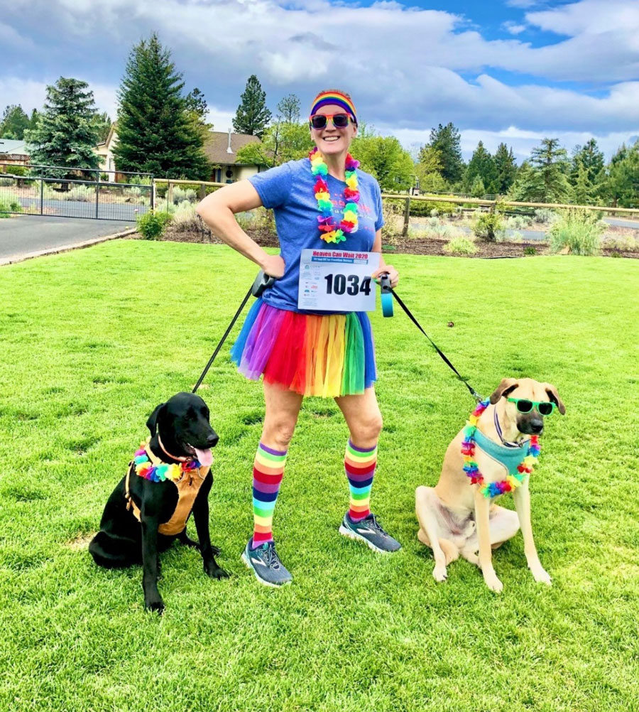 Woman dressed in rainbow skirt holding two dogs
